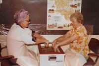 Två reumatikerdamer doppar händerna i vaxbad, gissar tidigt -70 tal.jpg