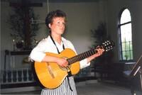 Musik i kyrkan. Åsa Eriksson (Nilsson) med gitarr och sång. Ca 1990.